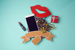 Smartphone with cardboard banner, lipstick and gift box. Creative website hero image. Stock Photos