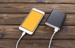 Smartphone, caricatore su un fondo di legno fotografia stock libera da diritti