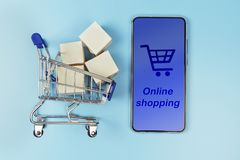 Smartphone and cart with boxes on blue background. The concept of on the Internet store royalty free stock photo