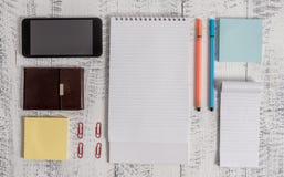 Smartphone, cartera del hombre, notas pegajosas, clips, cuaderno espiral, bol?grafos de las plumas, viejo r?stico de mentira del  foto de archivo