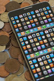 Smartphone on cash pile. Isolated smartphone, showing app programing concept on screen, cash background Royalty Free Stock Image