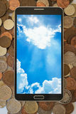 Smartphone on cash pile. Smartphone, showing cloud computing concept on screen, cash background Royalty Free Stock Photo