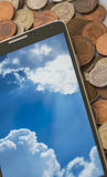 Smartphone on cash pile. Smartphone, showing cloud computing concept on screen, cash background Stock Photo