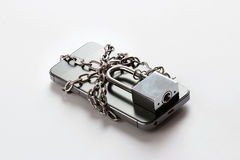 Smartphone with chain locked on white background Stock Photography