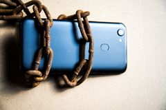 Smartphone in chains. Old rusty chains. Black smartphone
