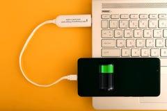 Smartphone chargeant par l'intermédiaire de la banque de puissance de l'exposition d'icône de batterie sur l'écran sur le dessus  photos libres de droits
