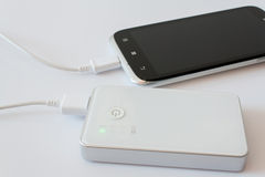 Smartphone charged by power bank Stock Photography