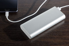 Smartphone charged by power bank Stock Photo