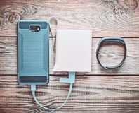 Smartphone is charged from the power bank, smart bracelet. On a wooden table. Modern gadgets royalty free stock photography