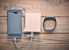 Smartphone is charged from the power bank, smart bracelet on a wooden table. Modern gadgets. Smartphone is charged from the power bank, smart bracelet on a royalty free stock image