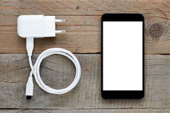 Smartphone and charger Royalty Free Stock Photography