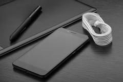 Smartphone, chargeur blanc avec trois ports USB et affichages, câble et comprimé graphique avec le stylet sur une table en bois photos stock
