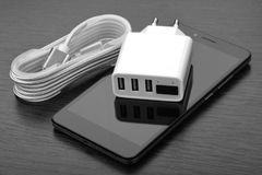 Smartphone, chargeur blanc avec trois ports USB et câble tressé dans la bobine sur une table en bois image libre de droits