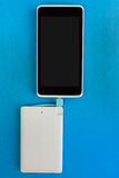 Smartphone charging with power bank on blue background Stock Photo