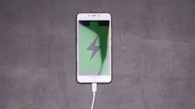 Smartphone charging stop motion animation. On a black background stock video