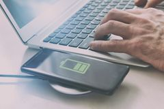 Smartphone charging on a wireless charger. Smartphone on a wireless charging pad, charger and hands on notebook keyboard royalty free stock images