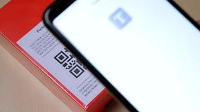 Smartphone che esplora codice di QR nell'etichetta di carta sul pacchetto o sulla scatola arancio del pacchetto video d archivio