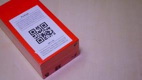 Smartphone che esplora codice di QR nell'etichetta di carta sul pacchetto o sulla scatola arancio del pacchetto stock footage