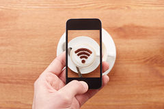Smartphone che prende fotografia del segno libero di wifi su un coffe del latte Fotografia Stock