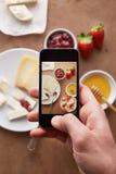 Smartphone che prende immagine della prima colazione Immagine Stock