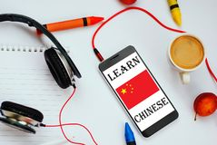 Learn chinese concept. Smartphone with chinese flag and headphones. concept of chinese learning through audio courses stock photos