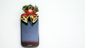 Smartphone and christmas bells Stock Photography