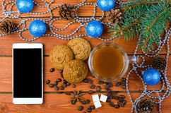Smartphone and Christmas decorations on a wooden table. Royalty Free Stock Photo