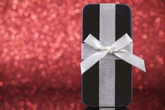 Smartphone for Christmas gift on red glitter background Stock Photos