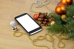 Smartphone and Christmas tree on wooden background. Christmas gr Stock Images