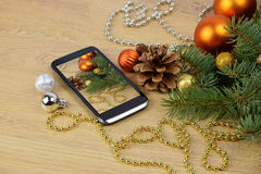 Smartphone and Christmas tree on wooden background. Christmas gr Stock Photos