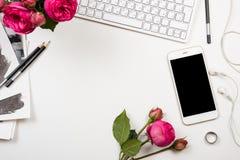 Smartphone, clavier d'ordinateur et fleurs roses de fesh sur l'étiquette blanche photographie stock libre de droits