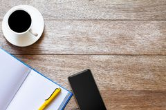Smartphone,coffee cup,notebook and pen on working vintage wooden table stock photos