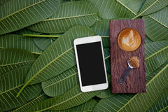 Smartphone and coffee on of green leaves. Flat lay Stock Photography