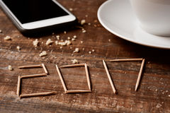 Smartphone, coffee and number 2017, as the new year. Toothpicks forming the number 2017, as the new year, on a rustic wooden table or a wooden bar next to a cup stock photography