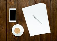 Smartphone, coffee and paper sheets Stock Image