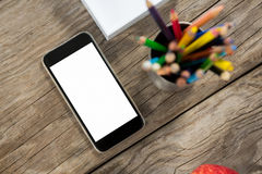 Smartphone and color pencils on wooden table Stock Images