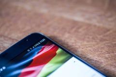 Smartphone com carga de 25 por cento e a bandeira alemão Fotos de Stock