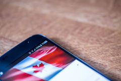 Smartphone com carga de 25 por cento e bandeira de Canadá Imagem de Stock Royalty Free