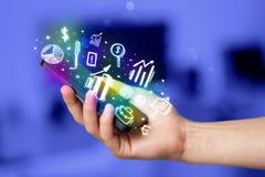 Smartphone com finança e ícones e símbolos do mercado Fotografia de Stock Royalty Free