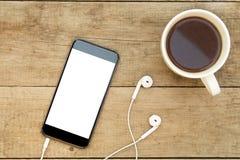 Smartphone com fones de ouvido e café na tabela de madeira foto de stock