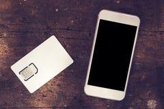 Smartphone com o cartão da tela vazia e do telefone celular SIM Foto de Stock