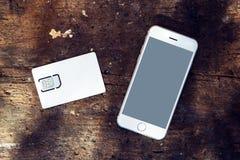 Smartphone com o cartão da tela vazia e do telefone celular SIM Fotografia de Stock Royalty Free