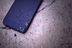 Smartphone com o tela táctil quebrado no assoalho concreto Imagens de Stock