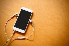 Smartphone com tela vazia e fones de ouvido no fundo de madeira fotografia de stock