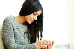 Smartphone commovente della giovane donna felice a casa Fotografie Stock Libere da Diritti