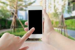 Smartphone commovente della mano della donna Immagini Stock Libere da Diritti