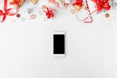 Smartphone composition for christmas time. christmas gifts and decorations on white background. stock photos