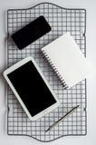 Smartphone, compressa e blocco note Immagine Stock