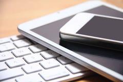 Smartphone, compressa e tastiera Immagine Stock