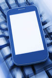Smartphone on the computer keyboard Stock Image